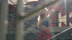 Pojawiać się blondynka z długie włosy w czerwonym czerń wierzchołku i spódnicie który stoi po środku schodków w w słońcu zbiory