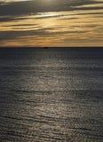 Pojedyncza łódź na oceanie przy zmierzchem Obrazy Royalty Free