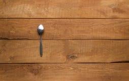 Pojedyncza łyżka na drewnianym stole Zdjęcia Stock