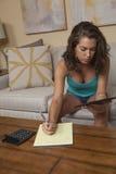 Pojedyncza dziewczyna pracuje na budżeta i wynagrodzeń rachunkach Fotografia Stock