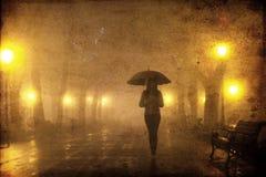 Pojedyncza dziewczyna z parasolem przy nocy aleją. Zdjęcia Stock