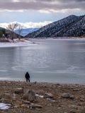 Pojedyncza, Odosobniona postać na brzeg Zamarznięty jezioro, Zdjęcie Royalty Free