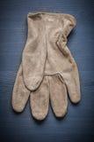 Pojedyncza pracująca rękawiczka na błękitnej drewnianej desce Obrazy Royalty Free