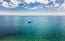 Pojedyncza skalista wyspa na spokojnym lazurowym błękitnym morzu Fotografia Royalty Free
