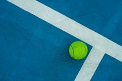 Pojedyncza tenisowa piłka na błękitnym tenisowym sądzie Zdjęcie Stock