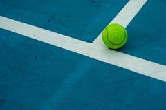 Pojedyncza tenisowa piłka na błękitnym tenisowym sądzie Fotografia Royalty Free