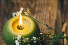 Pojedyncza zieleń kształtująca świeczka z suchym kwiatu paleniem na nieociosanym drewnianym stole w górę zdjęcie stock