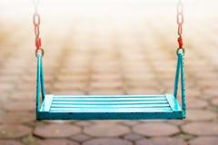 Pojedynczej błękit huśtawki puści ludzie w parka i plamy tle Zdjęcie Stock