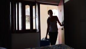 Pojedynczy kobieta czek w pokój hotelowego otwiera drzwi i przechodzi pokój zbiory