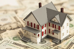 Pojedynczy rodzina dom na stosie pieniądze Zdjęcie Stock