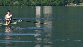Pojedynczy scull rower napędza brzeg, fachowa męska atleta wiosłuje łódź zbiory wideo