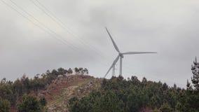 Pojedynczy silnik wiatrowy wiruje na górze między zielonymi drzewami przeciw niebu zdjęcie wideo