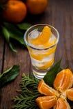 Pojedynczy szkło z świeżymi soczystymi dojrzałymi mandarynów Tangerines, lód Odbitkowa przestrzeń i zbliżenie na ciemnym tle Odgó Zdjęcie Royalty Free