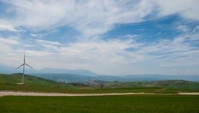 Pojedynczy wiatraczek i wioska ono ximpx przeciw chmurnemu niebu Obrazy Royalty Free