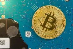 Pojedynczy złoty bitcoin na zielonych elektronika na dysku twardym zdjęcia stock