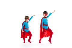 Pojkar är utklädda som en superhero och att peka upp med en maskering och en kappa royaltyfria foton