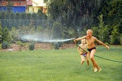 pojkar arbeta i trädgården spelrumvatten Arkivbilder