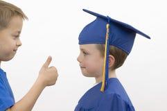 pojkar avlägger examen lyckligt arkivbilder