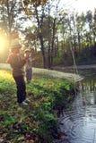 pojkar går att fiska på floden Arkivfoton
