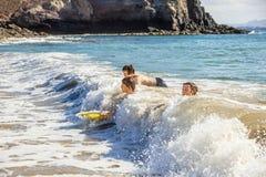 Pojkar har gyckel i havet med deras boogiebräden royaltyfri fotografi