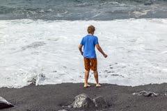 Pojkar har gyckel på den svarta stranden Arkivbild