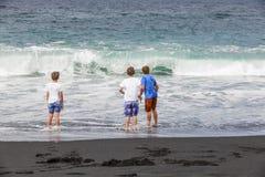 Pojkar har gyckel på den svarta stranden Royaltyfria Foton