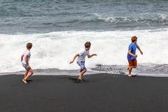 Pojkar har gyckel på den svarta stranden Arkivfoton