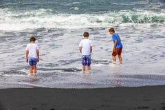 Pojkar har gyckel på den svarta vulkaniska stranden Royaltyfria Foton