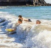 Pojkar har gyckel som surfar med deras boogiebräden Fotografering för Bildbyråer