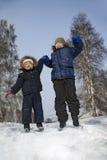 pojkar hoppar i vinter utomhus Arkivfoto