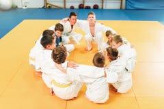 Pojkar i kimonosammanträde på golvet, judoutbildning arkivfoton