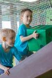 Pojkar lyfter stor tärning på kullen Aktiva lekar arkivbilder