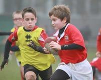 Pojkar med det röda/gula omslaget play rugby Royaltyfria Bilder