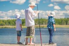pojkar med fadern på fiske i ett härligt ställe Arkivbild