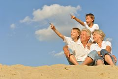 Pojkar med morföräldrar som sitter på sand Arkivbild