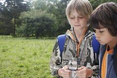 Pojkar med ryggsäckar genom att använda kompasset royaltyfri fotografi