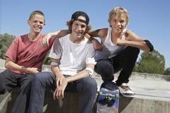 Pojkar med skateboarden som tillsammans sitter i skridsko, parkerar Royaltyfri Fotografi