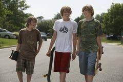 Pojkar med skateboarder som går på gatan Royaltyfria Bilder
