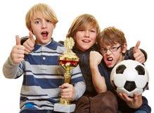 Pojkar med trofén och fotboll klumpa ihop sig Royaltyfria Bilder