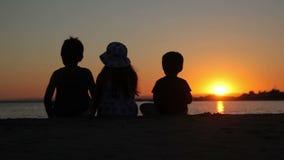 Pojkar och flickan håller ögonen på solnedgången över havet stock video