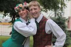 Pojkar och flickor i lettiska folk dräkter Arkivbilder