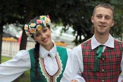 Pojkar och flickor i lettiska folk dräkter Arkivbild