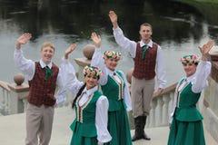Pojkar och flickor i lettiska folk dräkter Arkivfoton