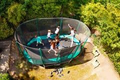 Pojkar och flickor som hoppar på trampolinen i trädgården royaltyfria bilder