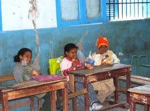 Pojkar och flickor som sitter på deras skivor, skyggar och skrattar på en kurs i grupp på skolan i Egypten Royaltyfri Bild