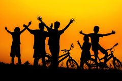 Pojkar och flickor som står och sitter bak en cykel med solnedgångkonturn royaltyfri fotografi