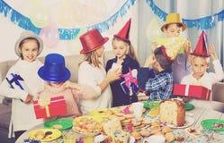 Pojkar och flickor som till varandra räcker gåvor under matställe Arkivfoto