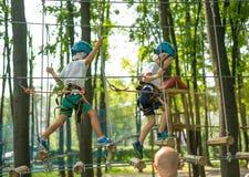 Pojkar på att klättra aktivitet i hög tråd Forest Park bröder två Tabellbergcablewayen lurar på sakkunniga igen Sherwood skog royaltyfria foton