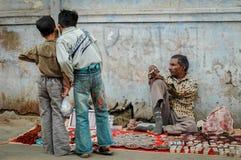 Pojkar på en utomhus- marknad arkivfoton