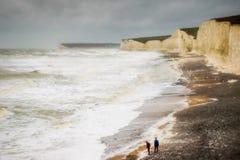Pojkar på stranden som stormen Desmond överför vågor för vitt vatten som kraschar på stranden Royaltyfri Fotografi